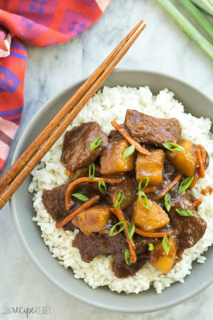 slow cooker mongolian beef with pineapple over white rice in a grey bowl with chopsticks on the side