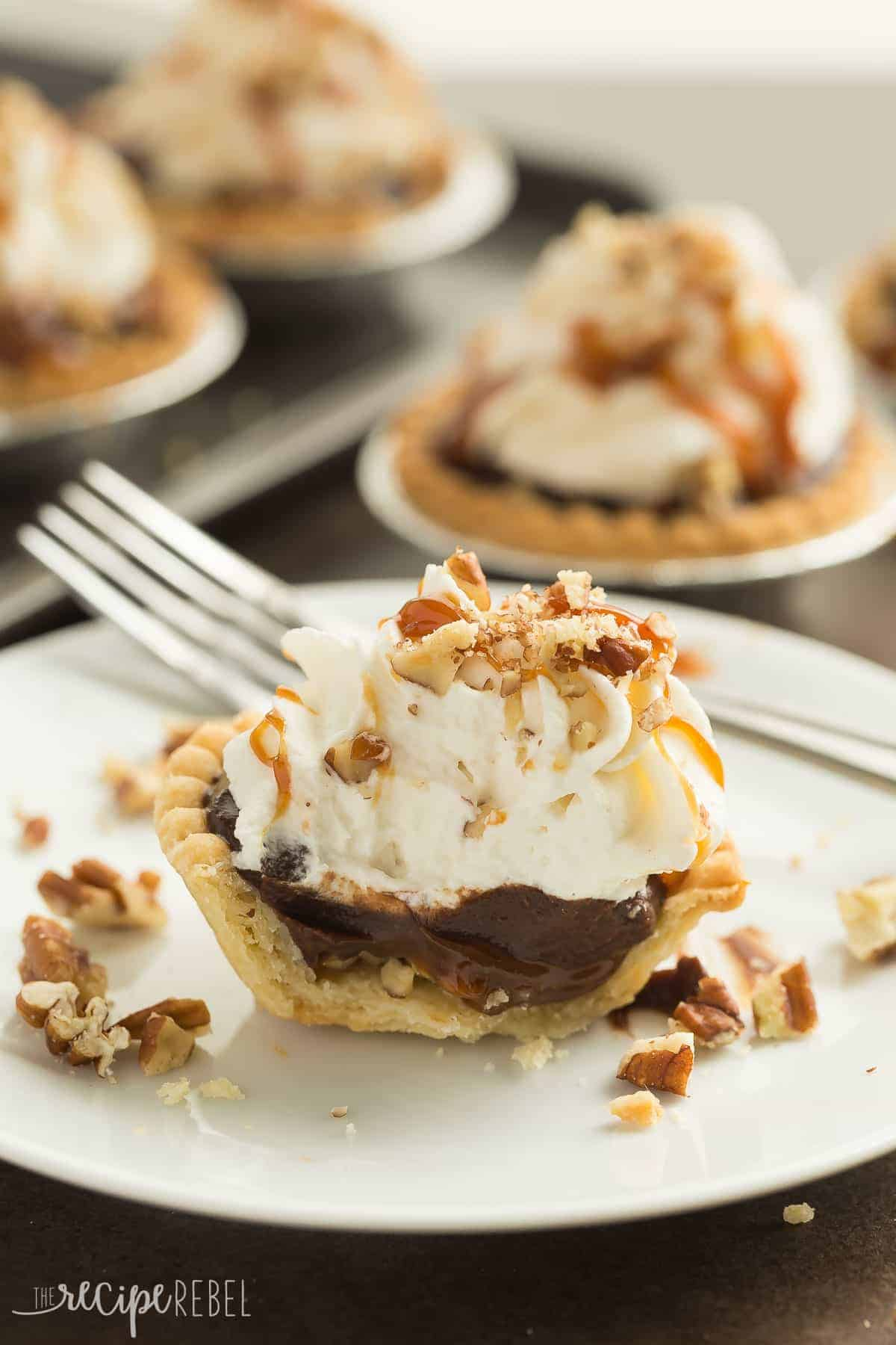 Turtle Pudding Pie Minis are the perfect bite-sized treat (made in tart shells!) for the holidays or any party -- they come together quickly and are loaded with pecans, caramel, chocolate pudding and topped with whipped cream!