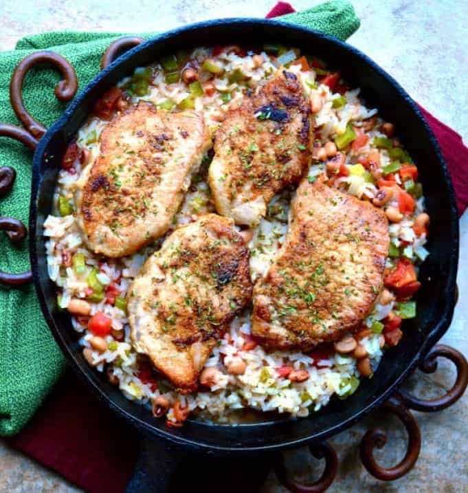 cast iron skillet with spicy pork chops on rice with vegetables and beans