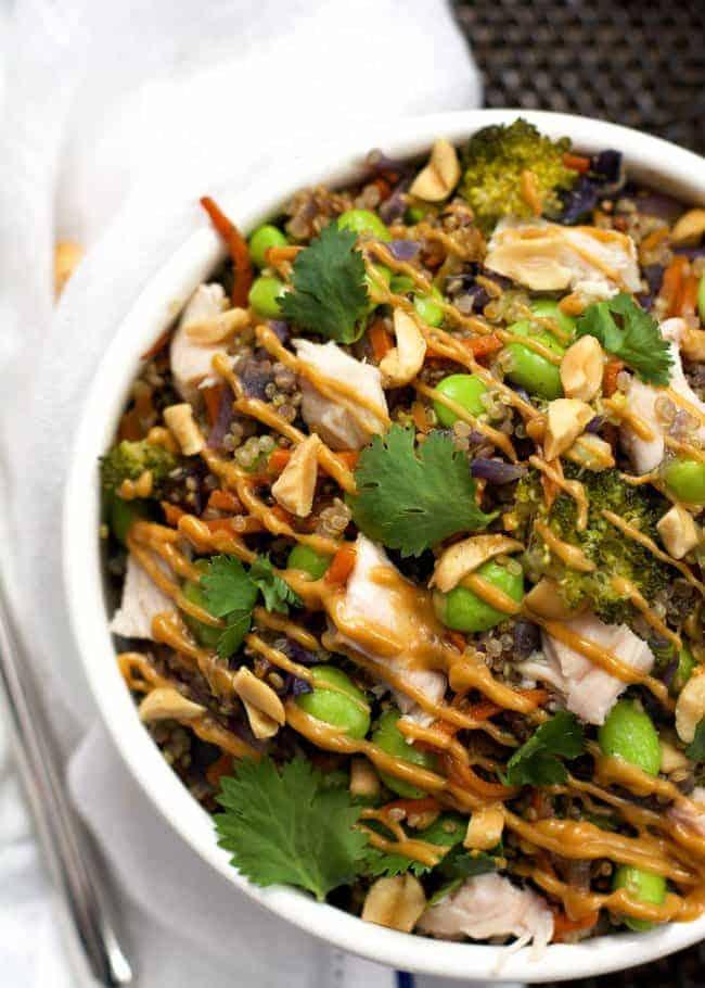 one pot thai quinoa bowls in white bowl with cilantro and drizzle of peanut sauce