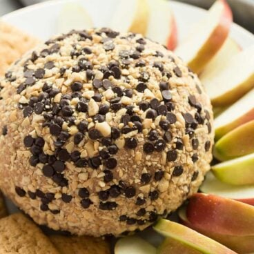 This Snickers Cheese Ball is an easy appetizer, snack or dessert -- filled with cream cheese, peanut butter, caramel and chocolate it is the BEST with apple slices! Perfect for potlucks.