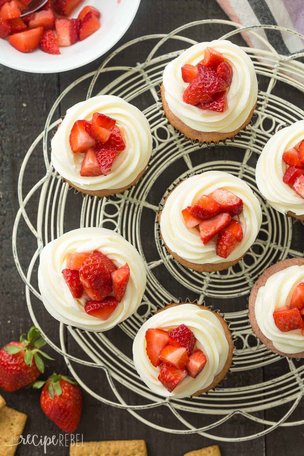 overhead image of a tray of strawberry cheesecake cupcakes with fresh chopped strawberries on top