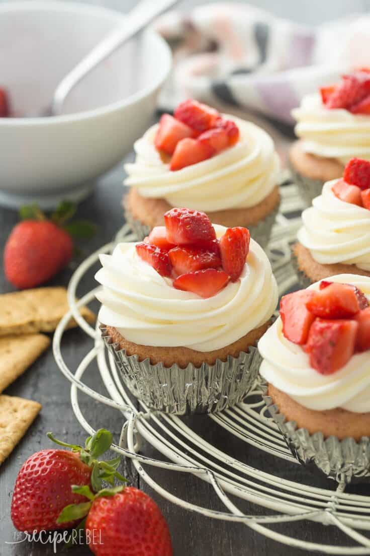 strawberry cheesecake cupcakes on white cooling rack with graham crackers and fresh strawberries on the side