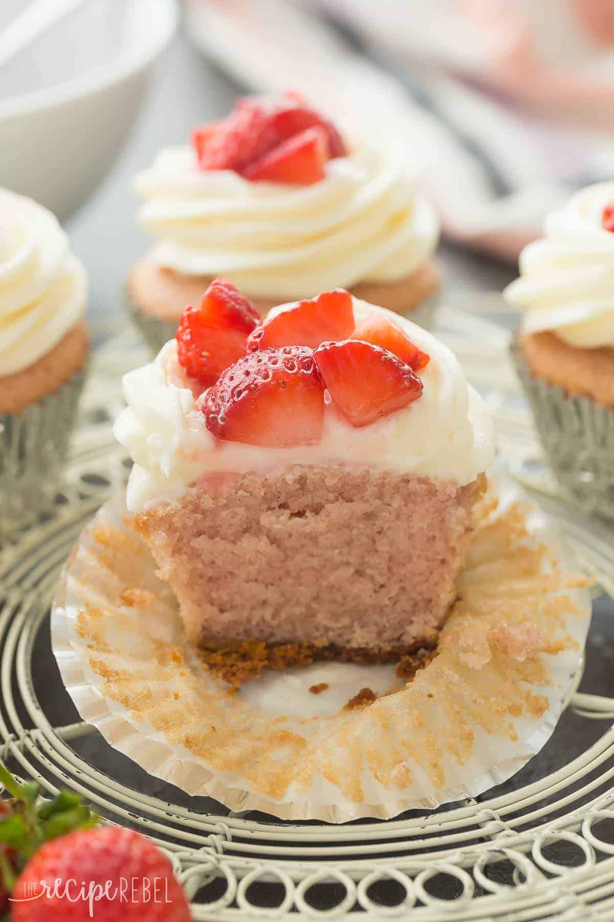 strawberry cheesecake cupcake cut in half to reveal pink cupcake and graham cracker crust on bottom