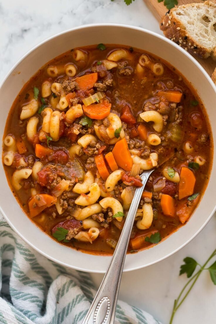 overhead image of beef tomato macaroni soup with spoon stuck in