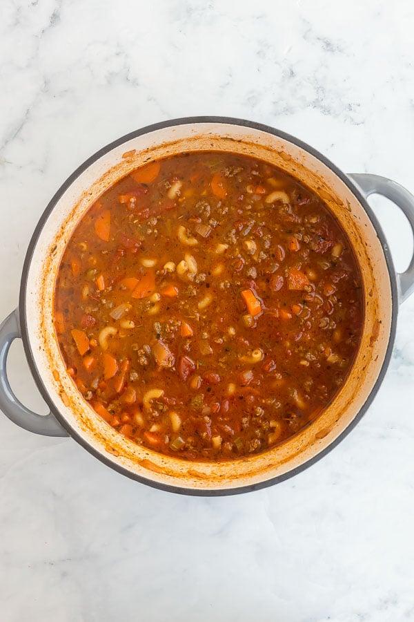 dry macaroni noodles added to tomato macaroni soup