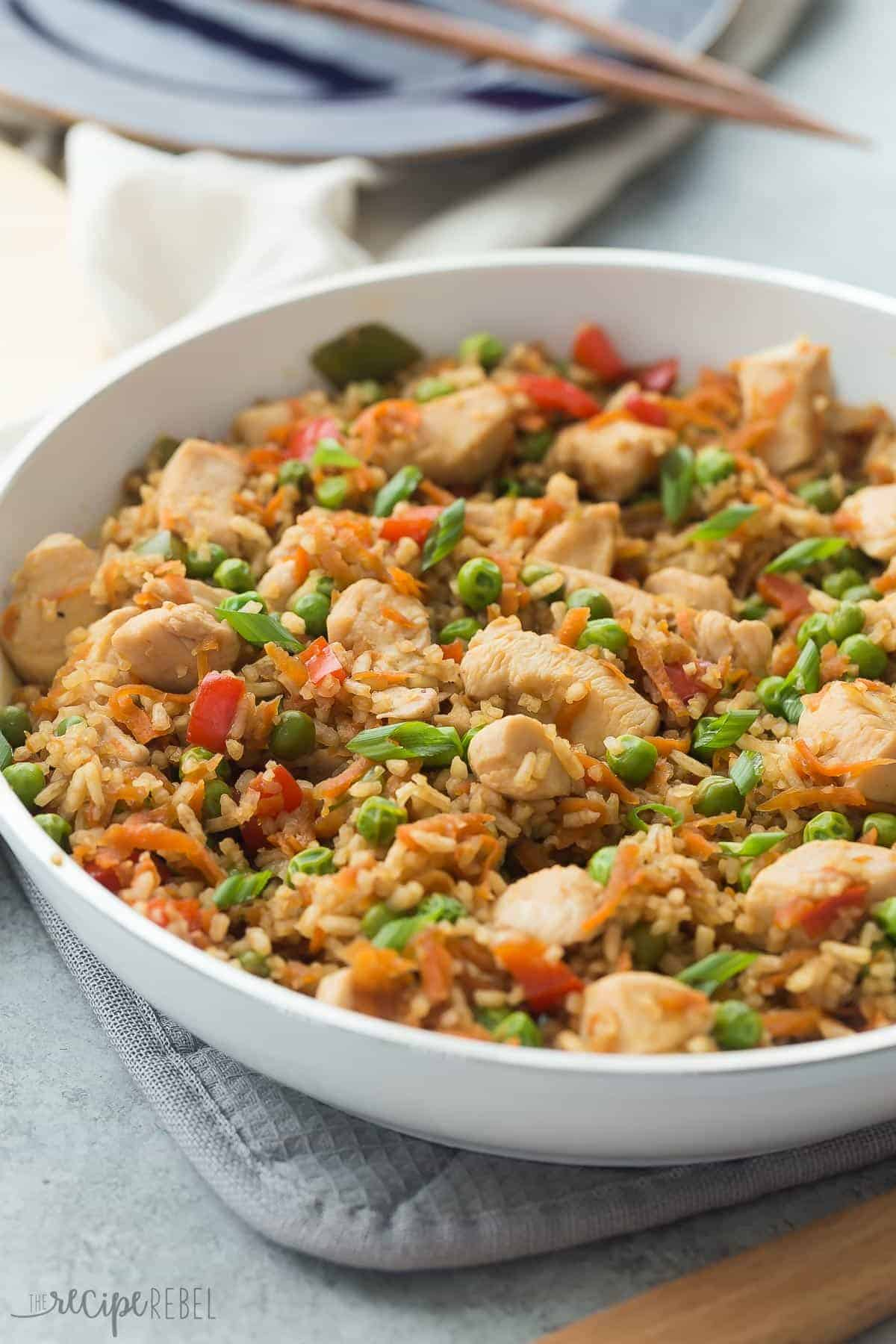 one pot teriyaki chicken rice and vegetables in white skillet with green onions on top