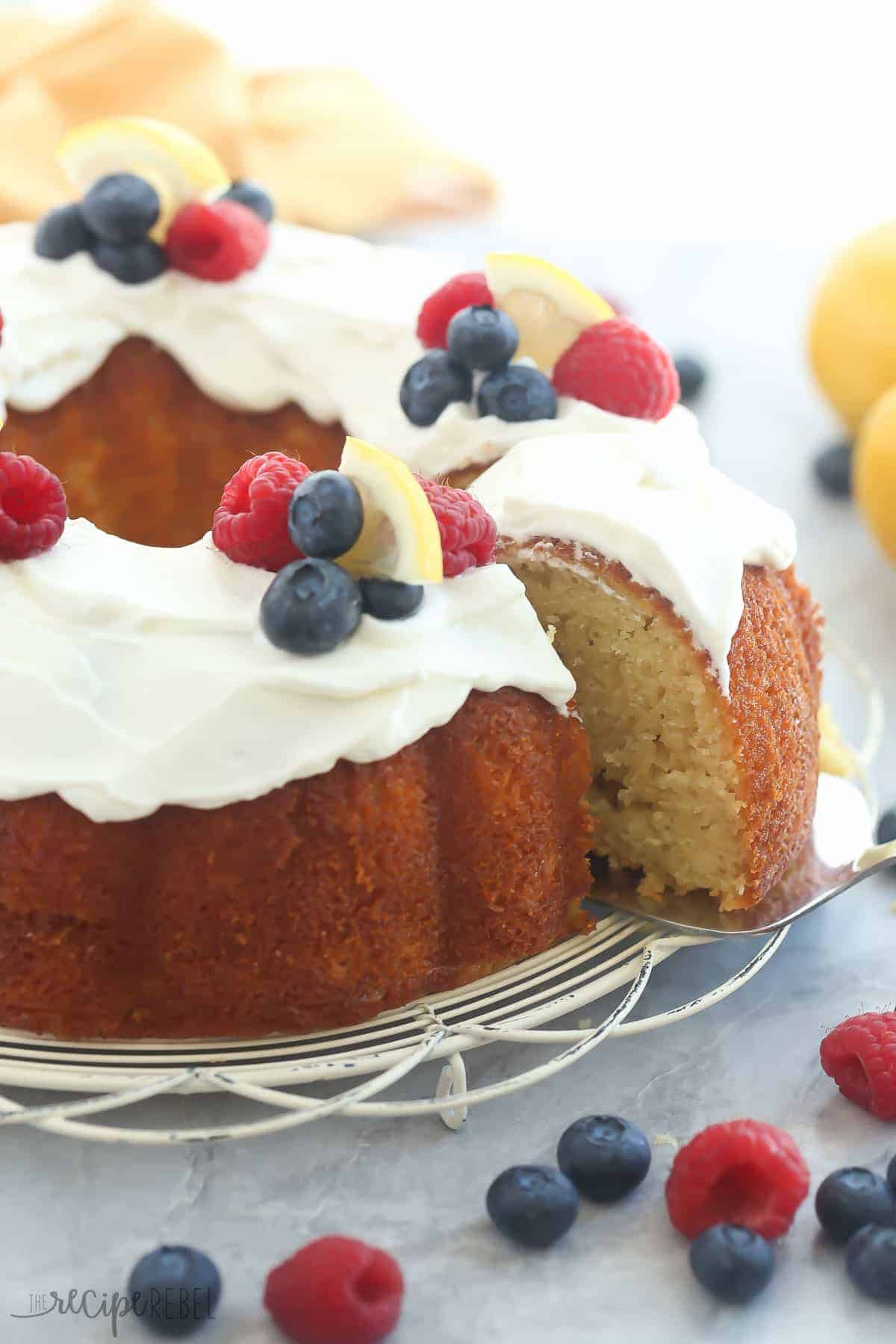 whole lemon bundt cake with whipped cream and berries with a piece being removed