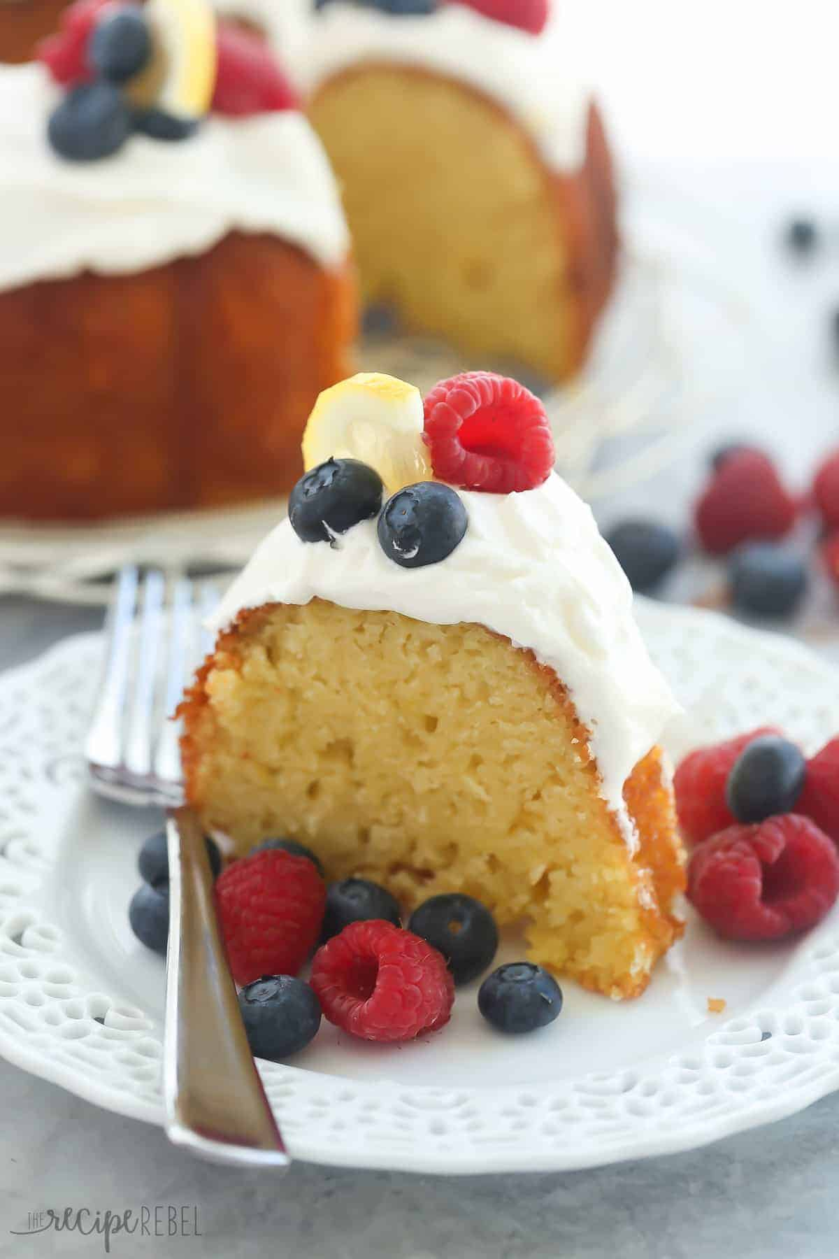 one slice of lemon bundt cake on white plate with whipped cream and berries