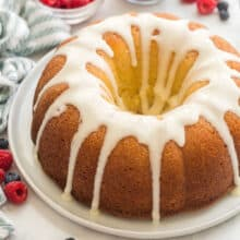 whole glazed lemon bundt cake with blueberries and raspberries in background