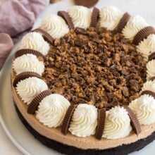 whole peanut butter cup cheesecake with whipped cream and chopped reeses