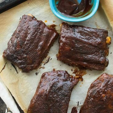 slow cooker bbq ribs in chunks on parchment lined baked sheet with bbq sauce