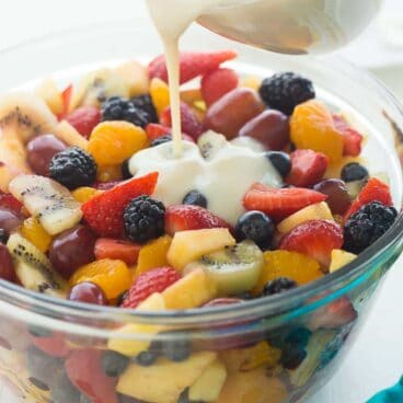 This Creamy Fruit Salad Recipe is made with a Homemade Vanilla Dressing -- no pudding mix here! It is the perfect summer breakfast, snack or dessert -- use whatever fruit you have! Includes step by step recipe video. | strawberries | blueberries | blackberries | grapes | pineapple | kiwi | summer salad | no bake dessert