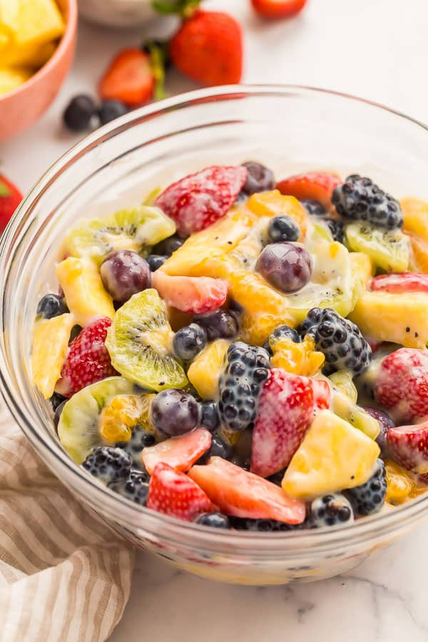 close up image of creamy fruit salad in glass bowl
