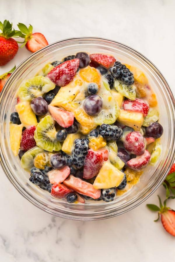overhead image of creamy fruit salad in glass bowl