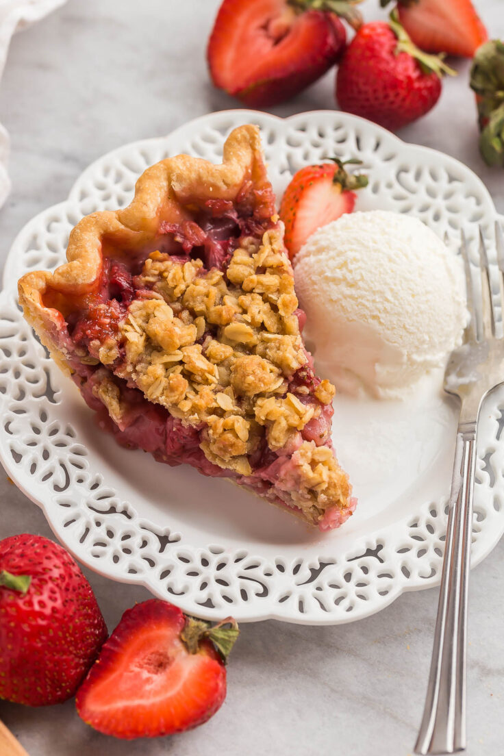 slice of strawberry pie on white plate with ice cream