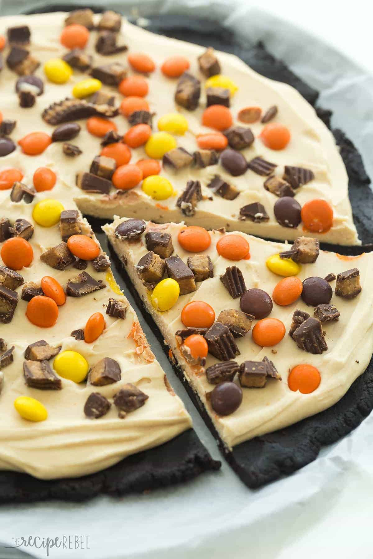 frozen peanut butter cup dessert pizza on pizza pan with one piece cut