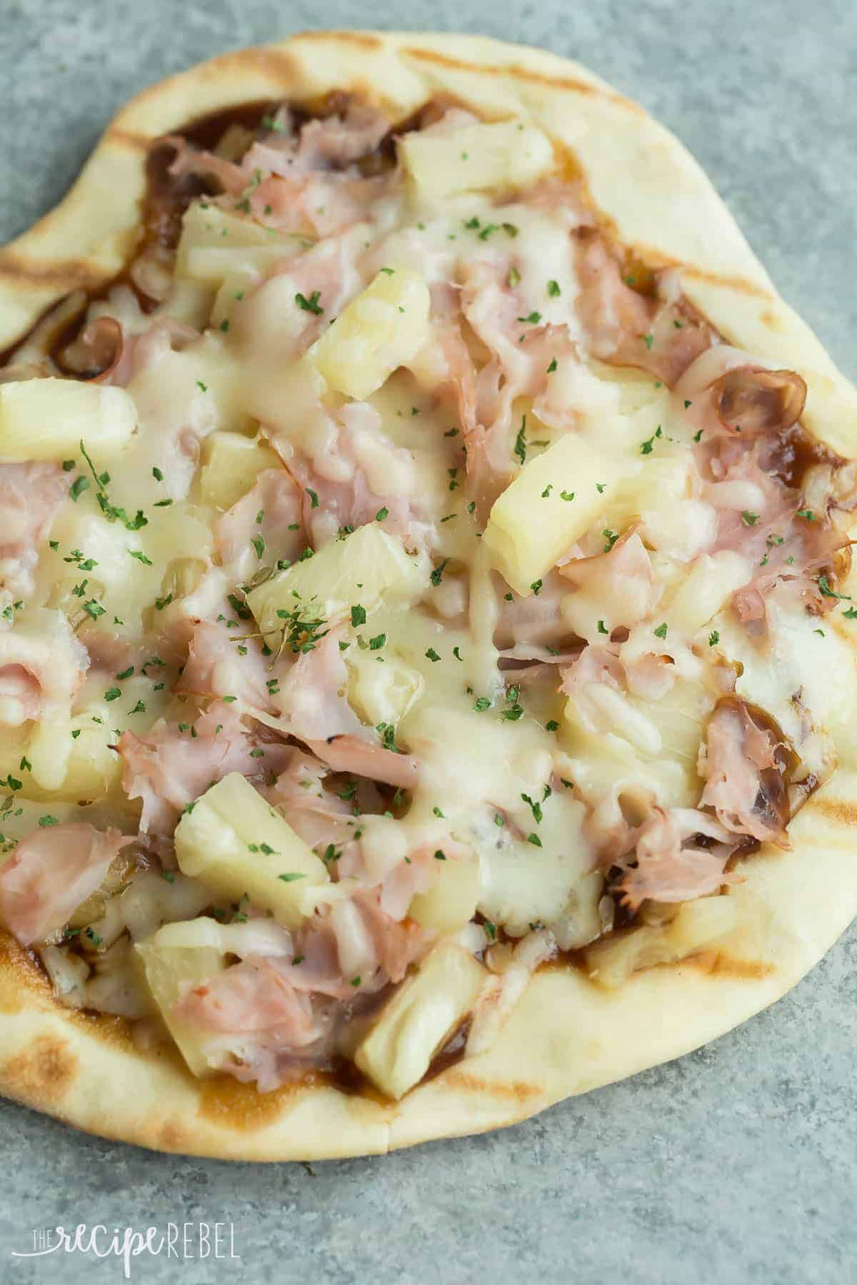 grilled bbq hawaiian pizza with ham pineapple and cheese on grey background