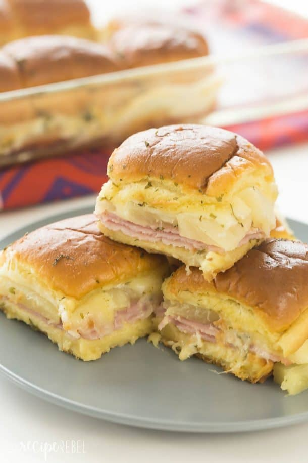 ham and pineapple sliders stacked on a grey plate with pan of sliders in the background