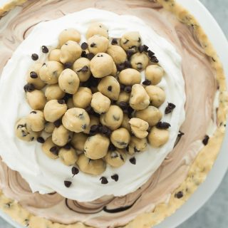 This Cookie Dough Ice Cream Cake is an easy, no bake dessert for a summer cookout or birthday party! Made on a cookie dough crust, filled with no churn ice cream and topped with chunks of cookie dough. Includes step by step recipe video | dessert recipe | cookie recipe | no bake dessert | summer | Easter | spring | birthday party