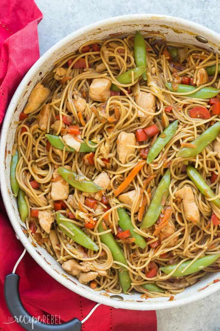 one pot chicken chow mein overhead on grey background with red towel on the side