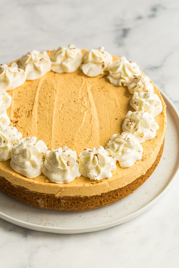 no bake pumpkin cheesecake whole on white plate with whipped cream