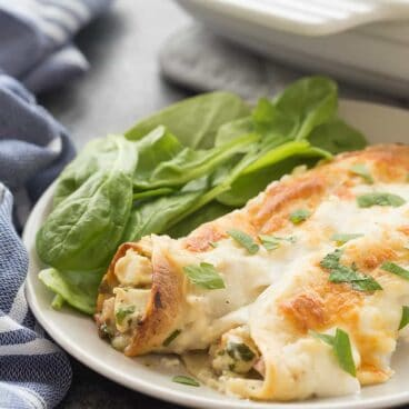 These Cordon Bleu Chicken Enchiladas are an easy, make ahead meal to keep on hand for busy weeknights! Loaded with chicken, ham, cheese and spinach, then smothered in Alfredo sauce and cheese, they are pure comfort food! Includes step by step recipe video. | easy recipe | make ahead dinner | freezer meal | freezer friendly | alfredo | chicken recipe