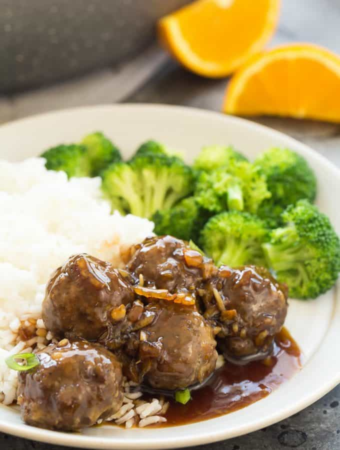 These Easy Meatballs in Orange Sauce have just a few ingredients and are perfect for a quick dinner, freezer meal, or even a holiday dinner or appetizer! Perfect over rice or with mashed potatoes. Includes step by step recipe video. | homemade meatball recipe | takeout | easy dinner recipe | weeknight meal | freezer meal