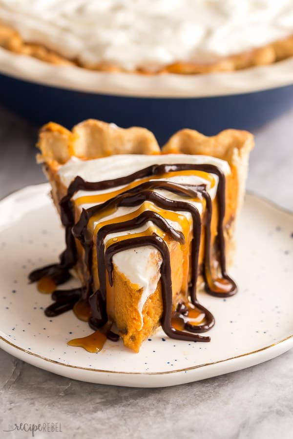 slice of turtle pumpkin pie on plate with chocolate and caramel drizzle