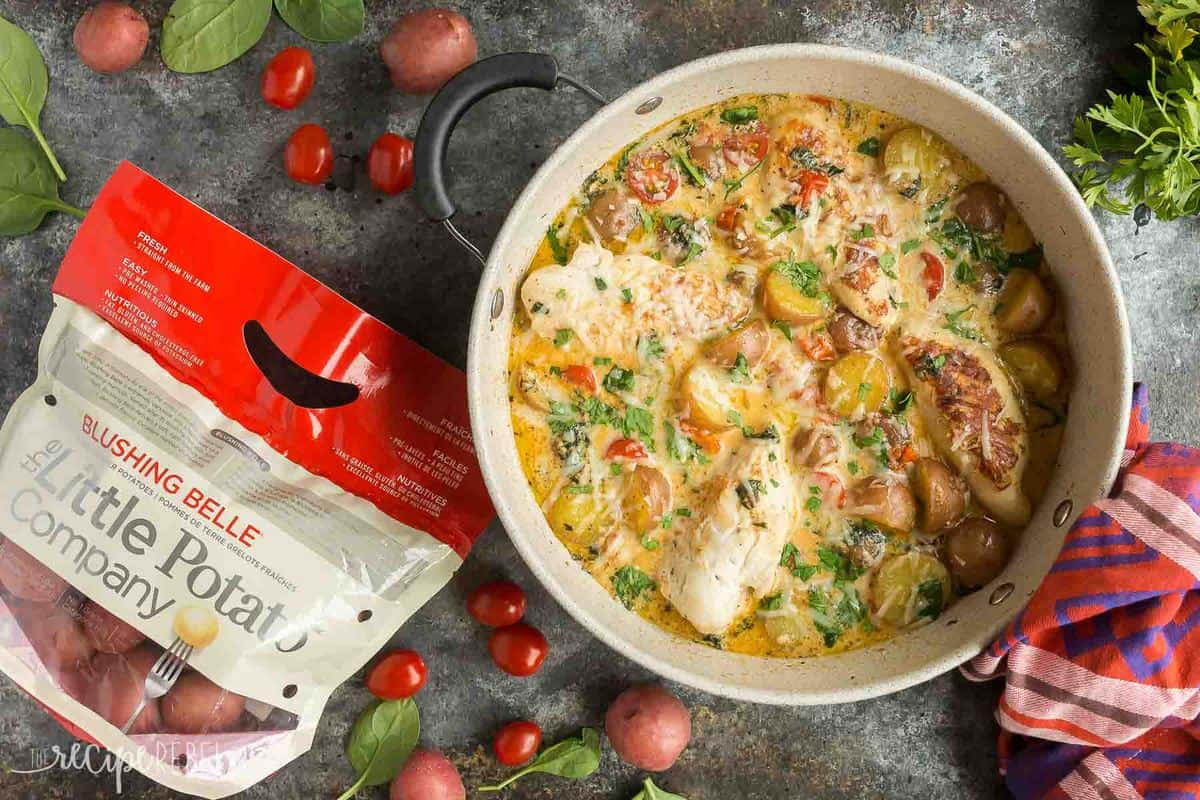 This One Pan Tuscan Chicken and Potato Skillet is an easy dinner idea that is loaded with flavor! With tomatoes, spinach, potatoes and a light Parmesan cream sauce, it's perfect one pot comfort food. Includes step by step recipe video. | chicken dinner | healthy dinner idea | one pot meal | one pan meal | italian chicken | gluten-free