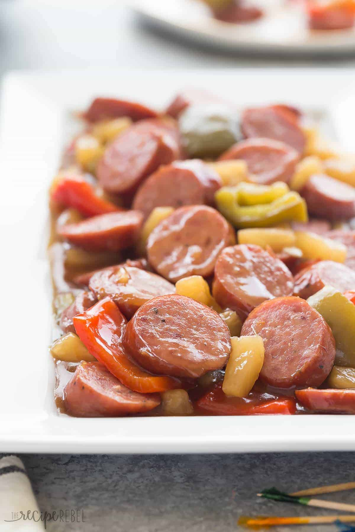 a long white plate with sliced smokies in sweet and sour sauce with pineapple and peppers