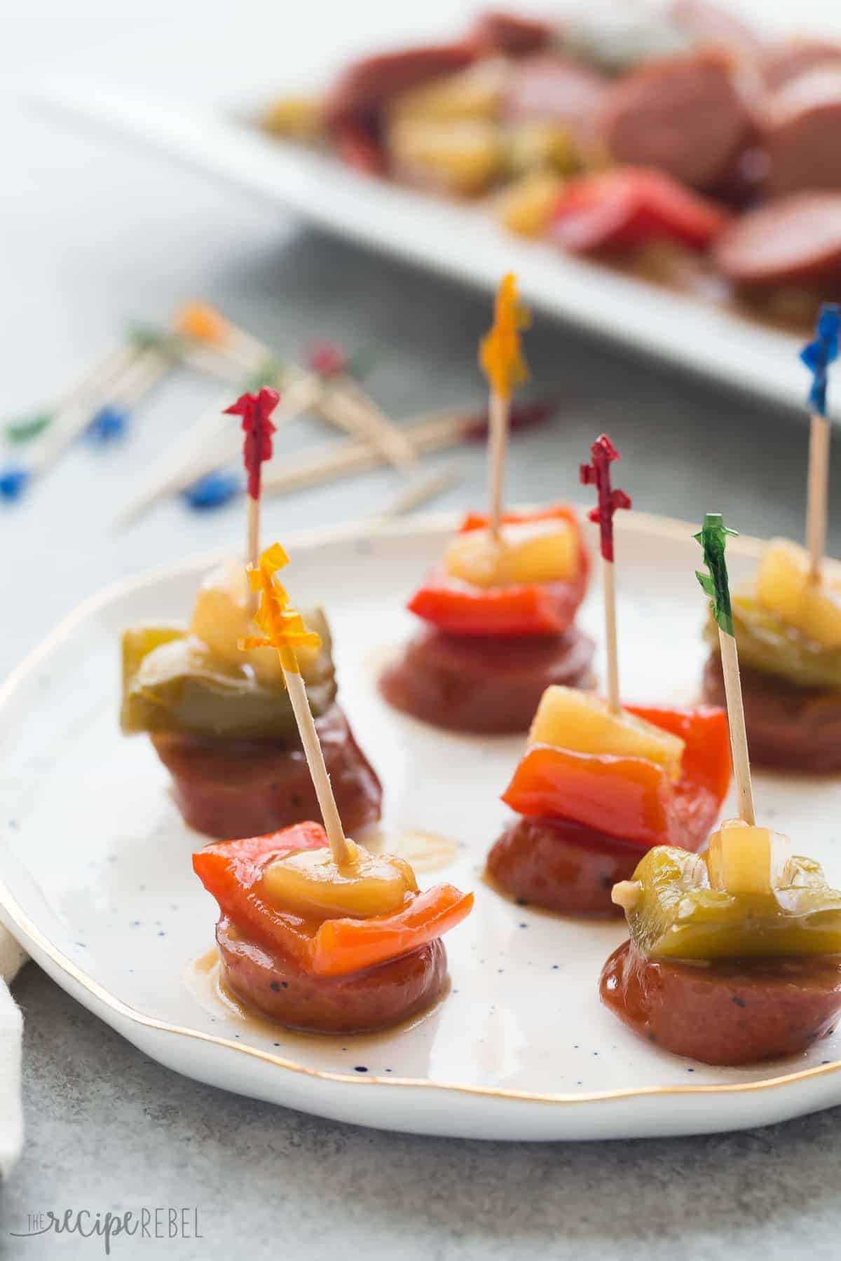 a white plate with sliced smokies and peppers on fancy toothpicks