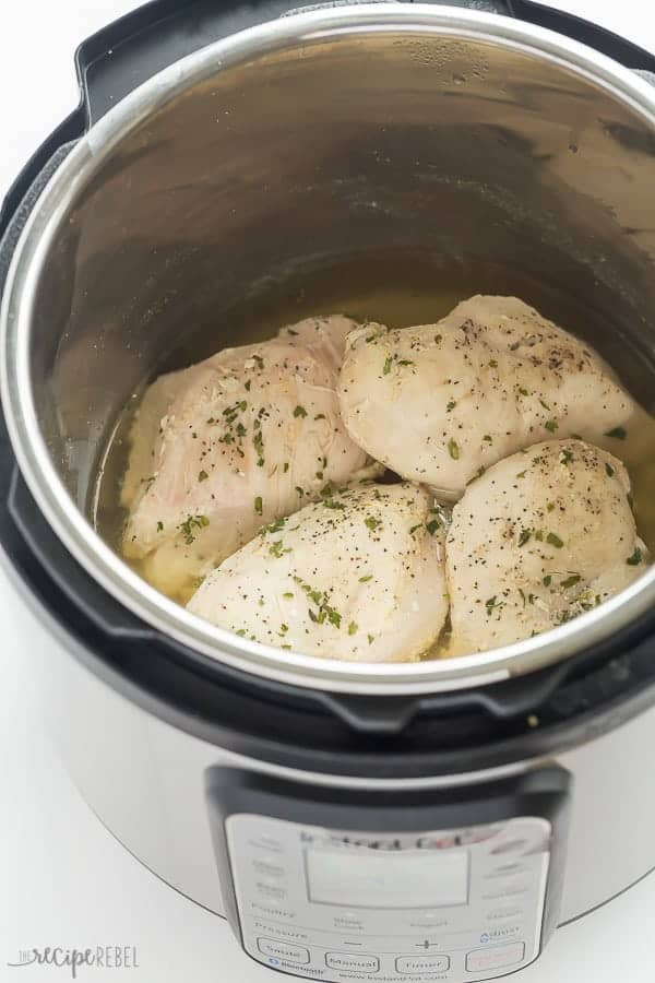 cooked chicken breasts in instant pot with seasonings and fresh herbs on top