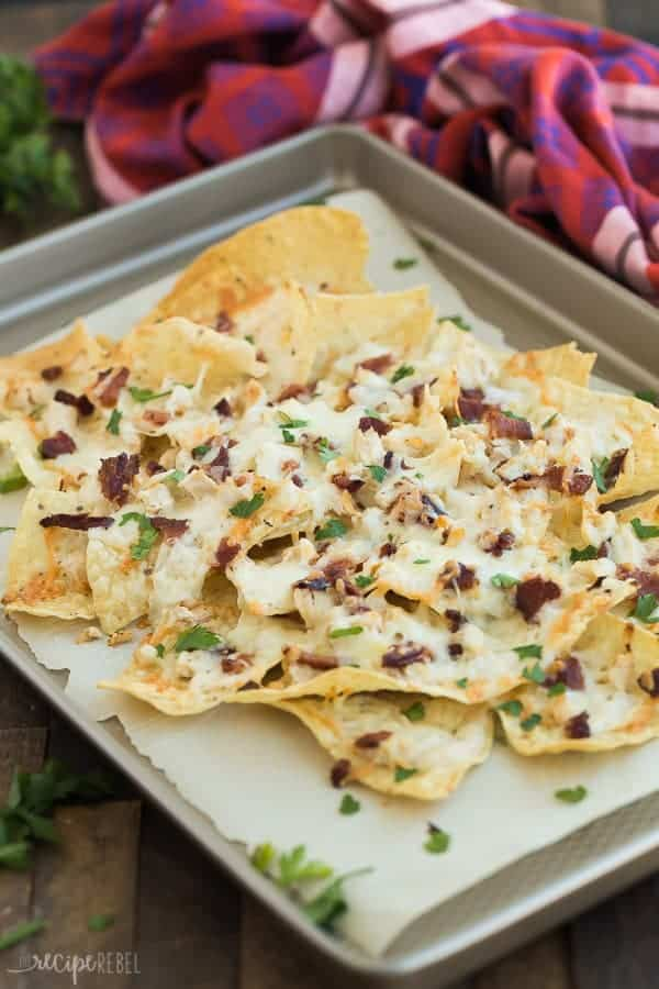 close up image of chicken alfredo nachos on sheet pan on wood background