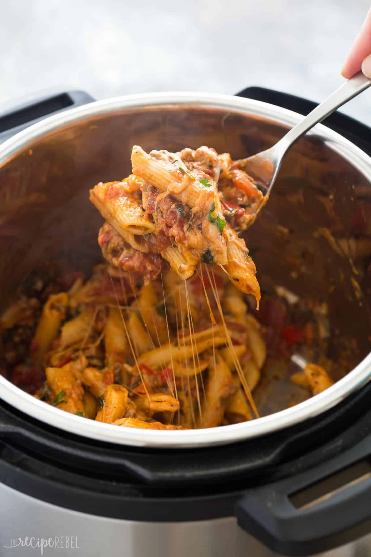 metal spoon scooping some instant pot baked ziti out of pressure cooker