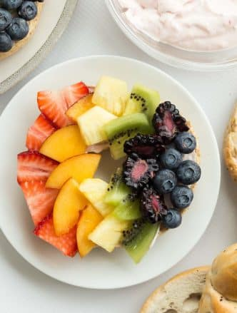 These Rainbow Bagel Fruit Pizzas with Strawberry Cream Cheese Spread are a fun breakfast or snack! Topped with a homemade, naturally sweetened strawberry cream cheese spread and fresh fruit that the kids (and the rest of the family!) will love! A fun treat for Easter, St. Patrick's Day or any day! Includes step by step recipe video. #rainbowfood rainbow food #fruit #breakfast #brunch #creamcheese