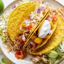 slow cooker chicken tacos in taco shells on plate piled with toppings