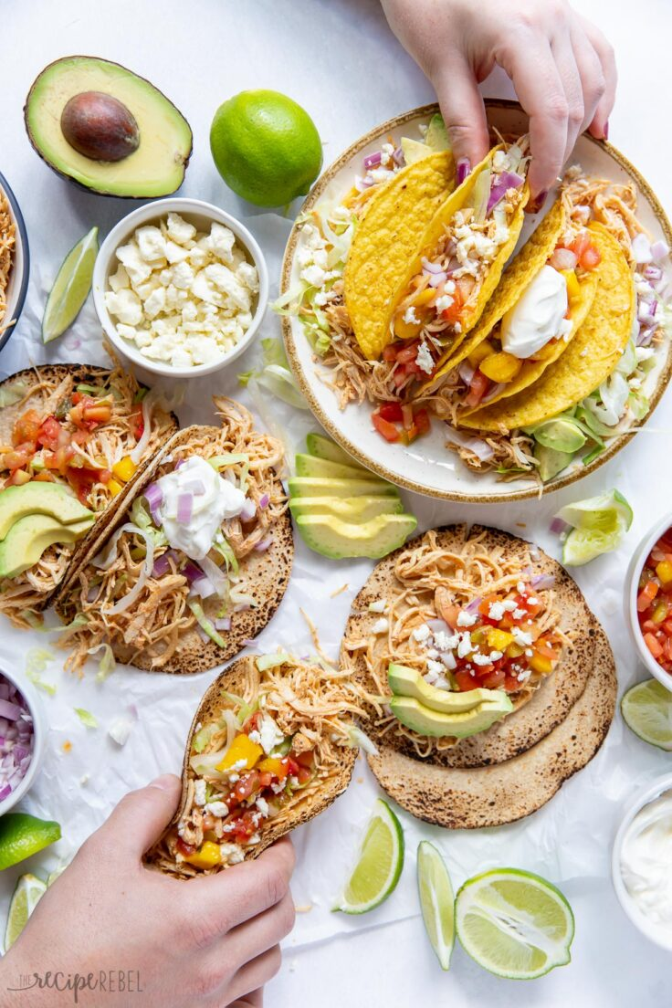 overhead image of crockpot chicken tacos and toppings in bowls