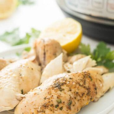 Instant Pot Whole Chicken on a white plate  This Instant Pot Whole Chicken recipe can be made with fresh or frozen chicken! It is moist, juicy and so much easier than roasting! Slathered in garlic butter and cooked to perfect in your pressure cooker in just 30 minutes.