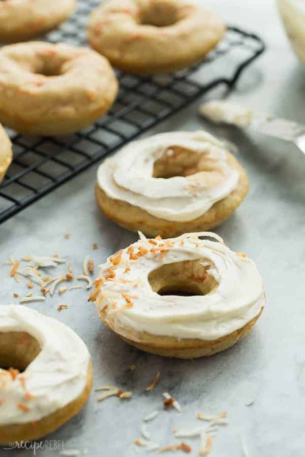carrot cake baked donuts on marble with cream cheese frosting and toasted coconut
