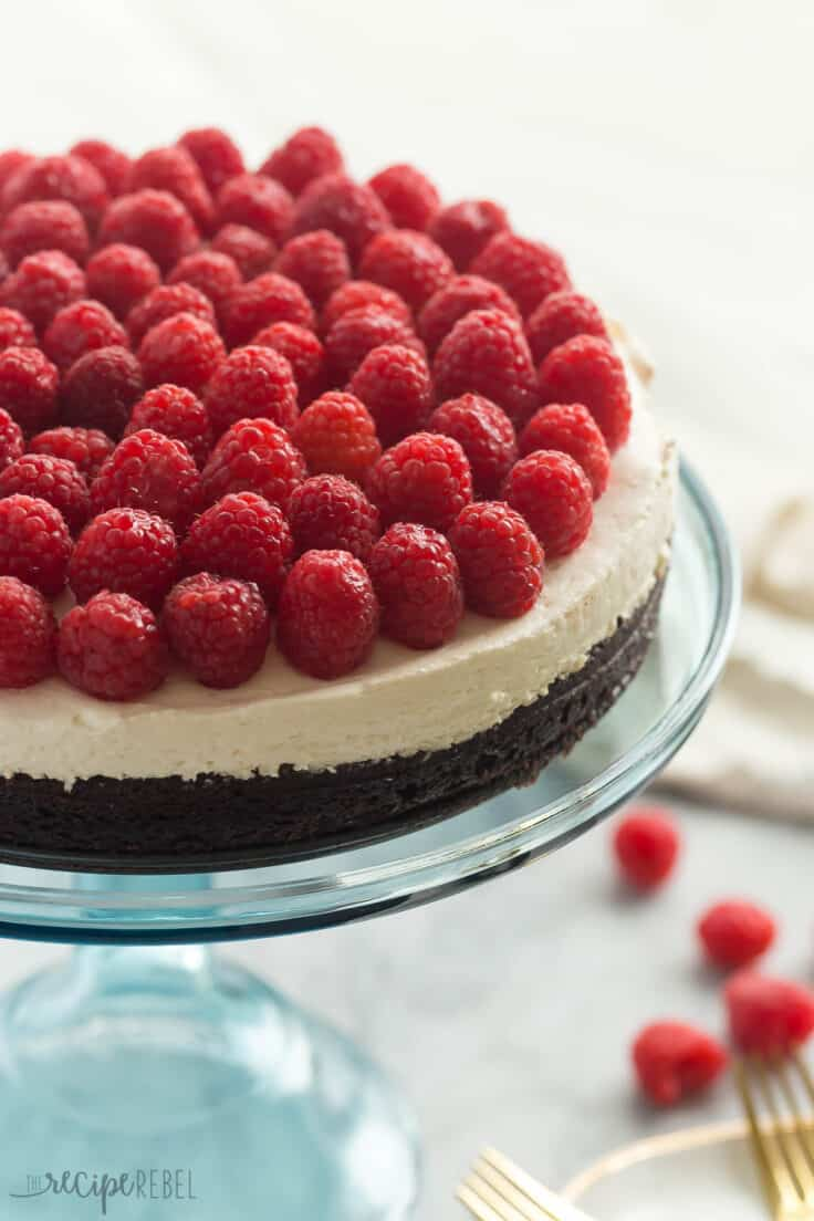 whole brownie bottom cheesecake on blue cake plate topped with fresh raspberries