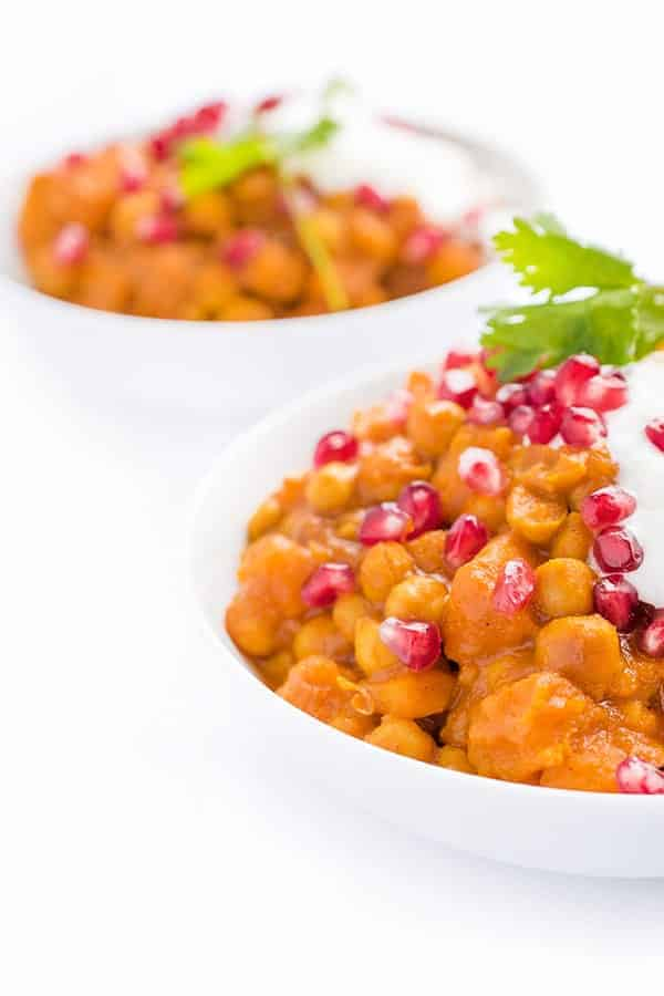 slow cooker vegetarian chickpea curry in white bowls with pomegranate arils topping
