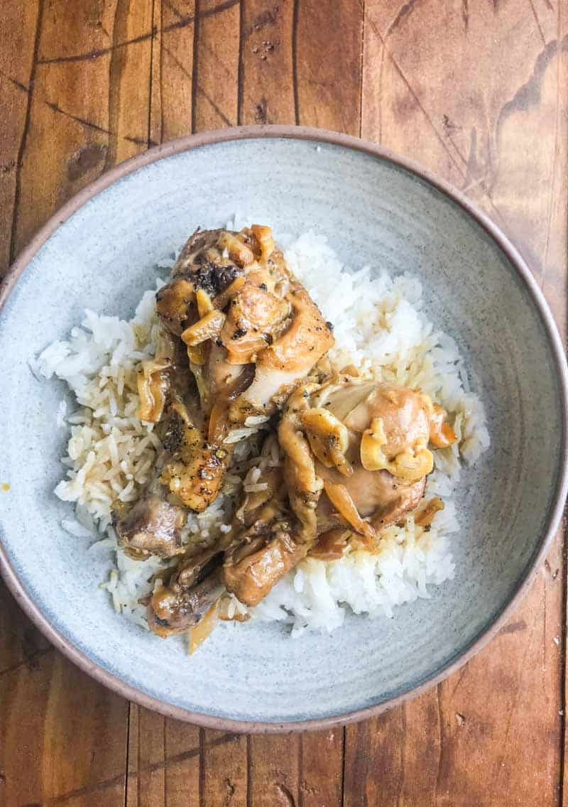 instant pot chicken adobo over rice on grey plate on wooden background