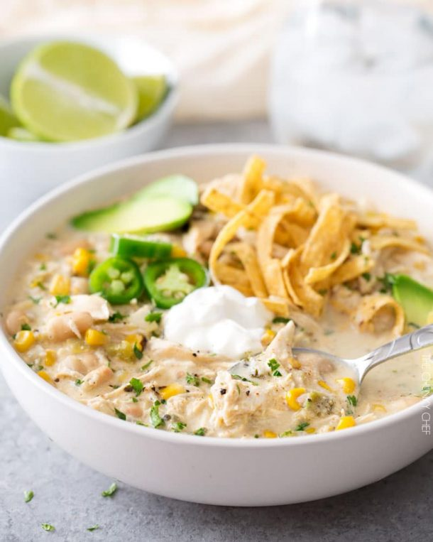 creamy crockpot white chicken chili in white bowl with jalapenos and sour cream