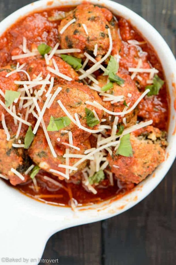 slow cooker turkey meatballs florentine in white bowl with shredded parmesan cheese