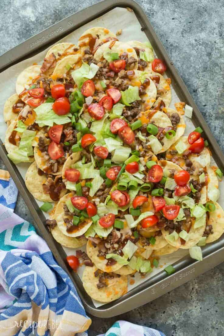 bbq bacon cheeseburger nachos overhead on sheet pan on grey background