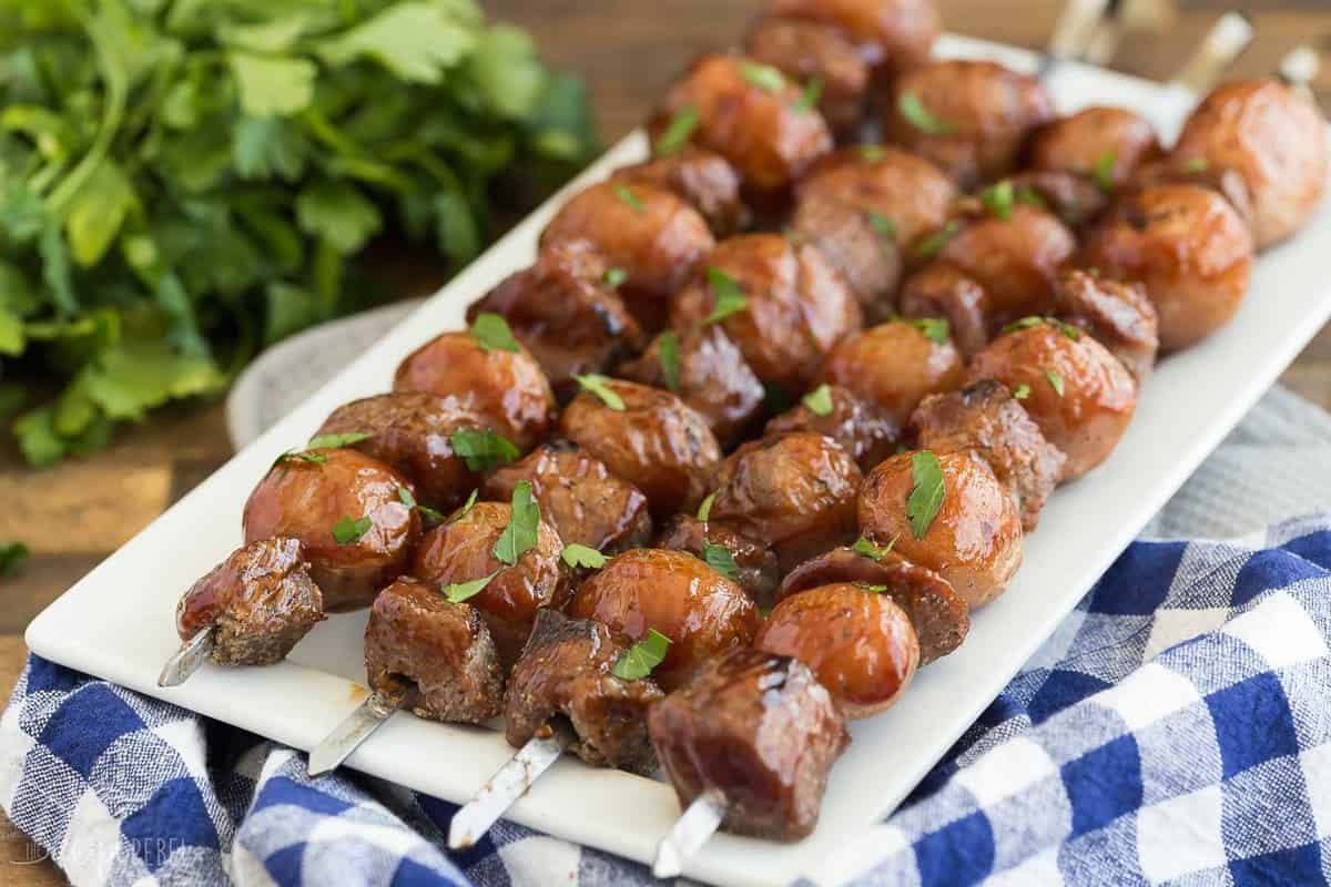 bbq steak and potato skewers on white plate with parsley bunch in the background