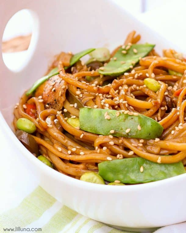 crock pot lo mein close up in white bowl topped with sesame seeds