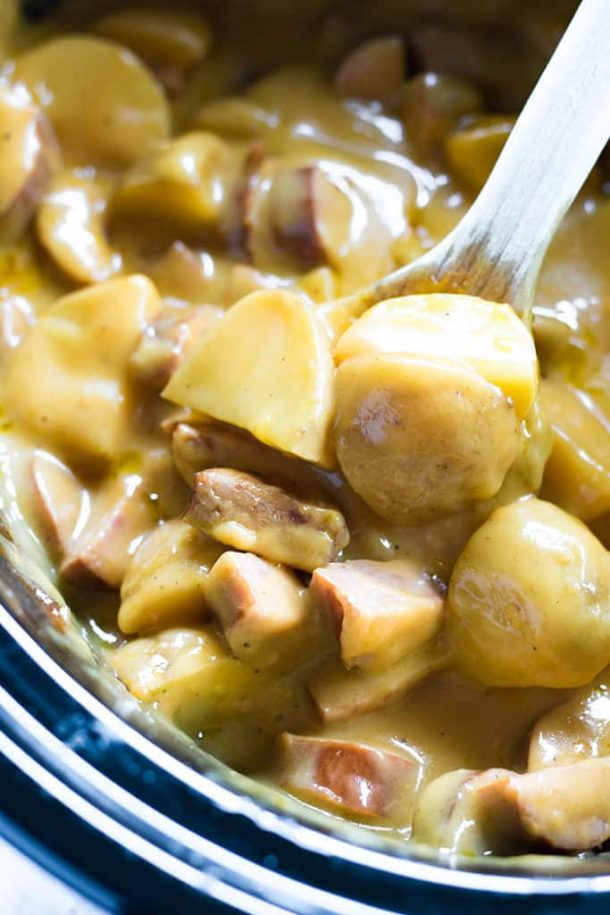 cheesy crockpot sausage and potatoes close up shot with wooden spoon