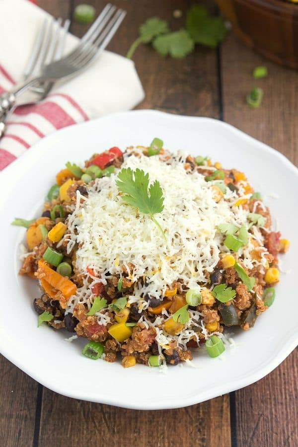 slow cooker quinoa tex mex on white plate topped with lots of shredded cheese